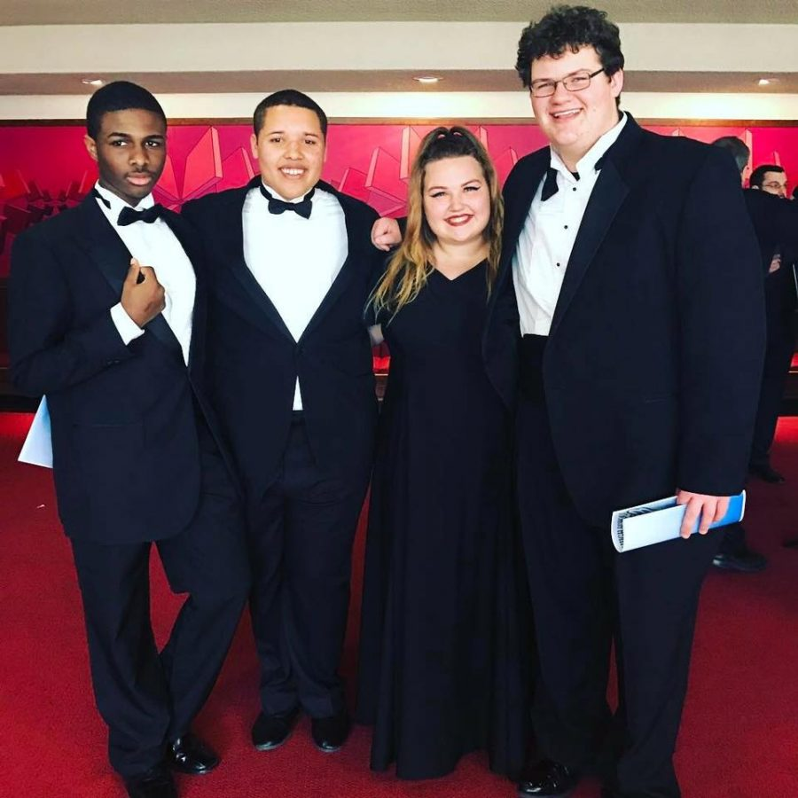 The four state choir members pose on the red carpet after the chamber choir KMEA performance.