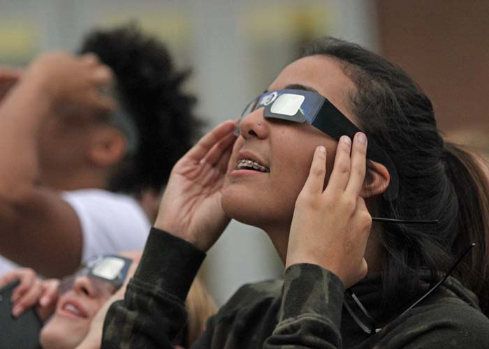 One student attempts to look through their glasses to get a glimpse of the sun