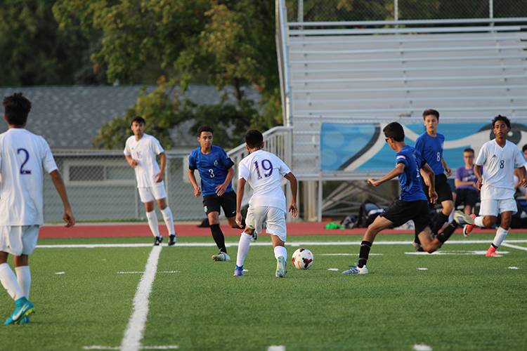 Senior Aaron Reutzel dribbling around defenders towards the goal.
