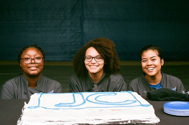 Culinary students posing in front of the special JC cake made special for the ground breaking ceremony.