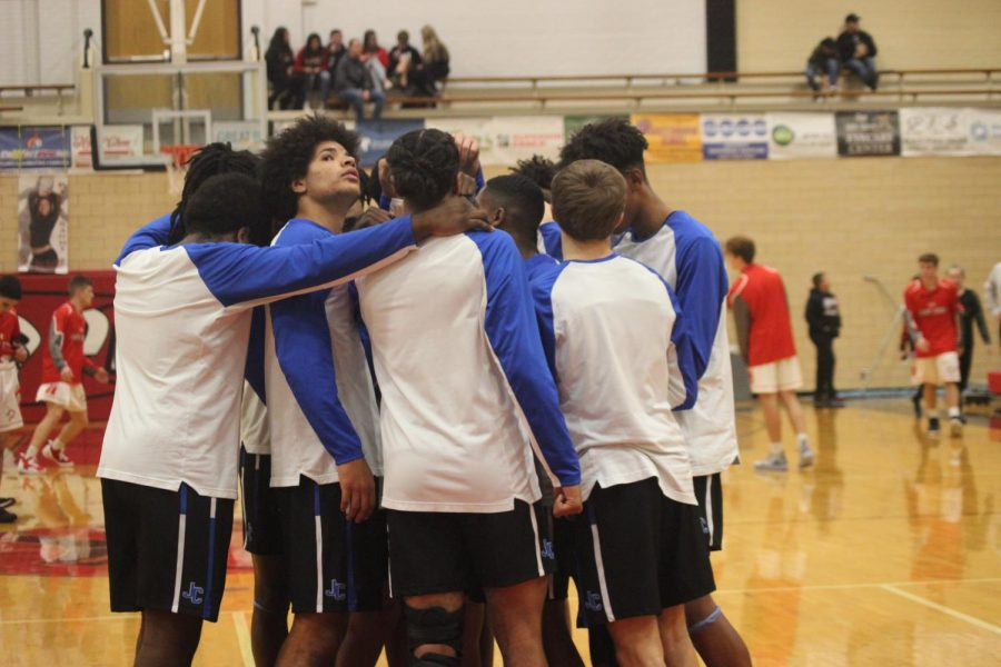 The varsity boys basketball team huddles up during warm ups at the game against Great Bend on Friday December 4th.