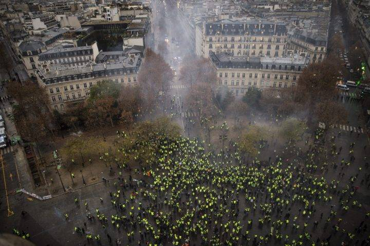 A+barricade+with+polices+forces+and+protesters+wearing+yellow+vests.+